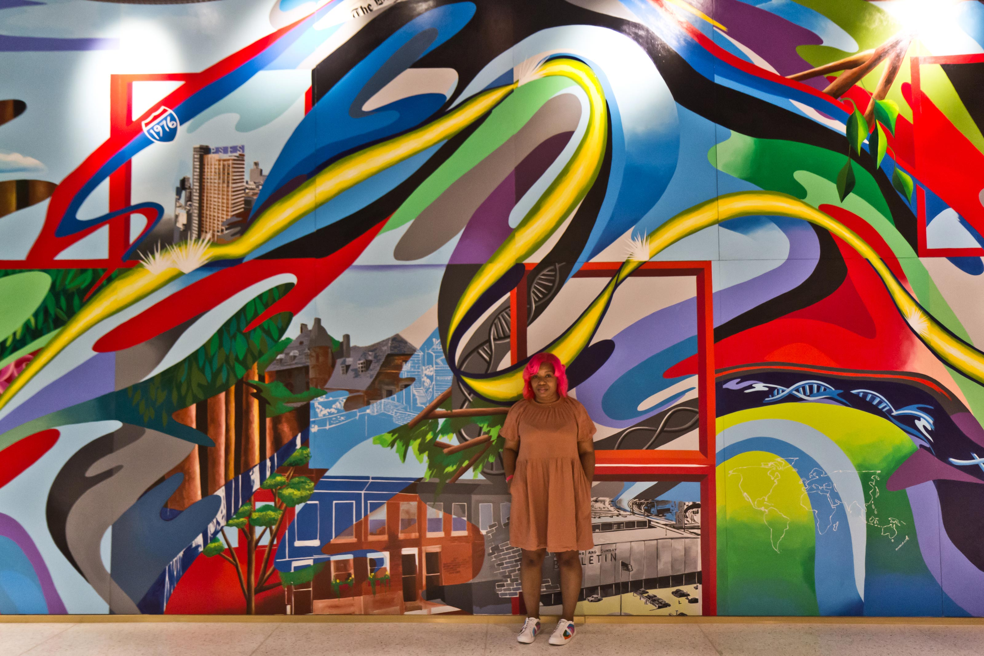 Artist Serena Saunders with her mural 'The Path' at the Bulletin Building across from 30th Street Station in Philadelphia. (Kimberly Paynter/WHYY)