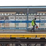A worker uses a leaf blower to move trash onto the tracks at Allegheny SEPTA station. (Kimberly Paynter/WHYY)
