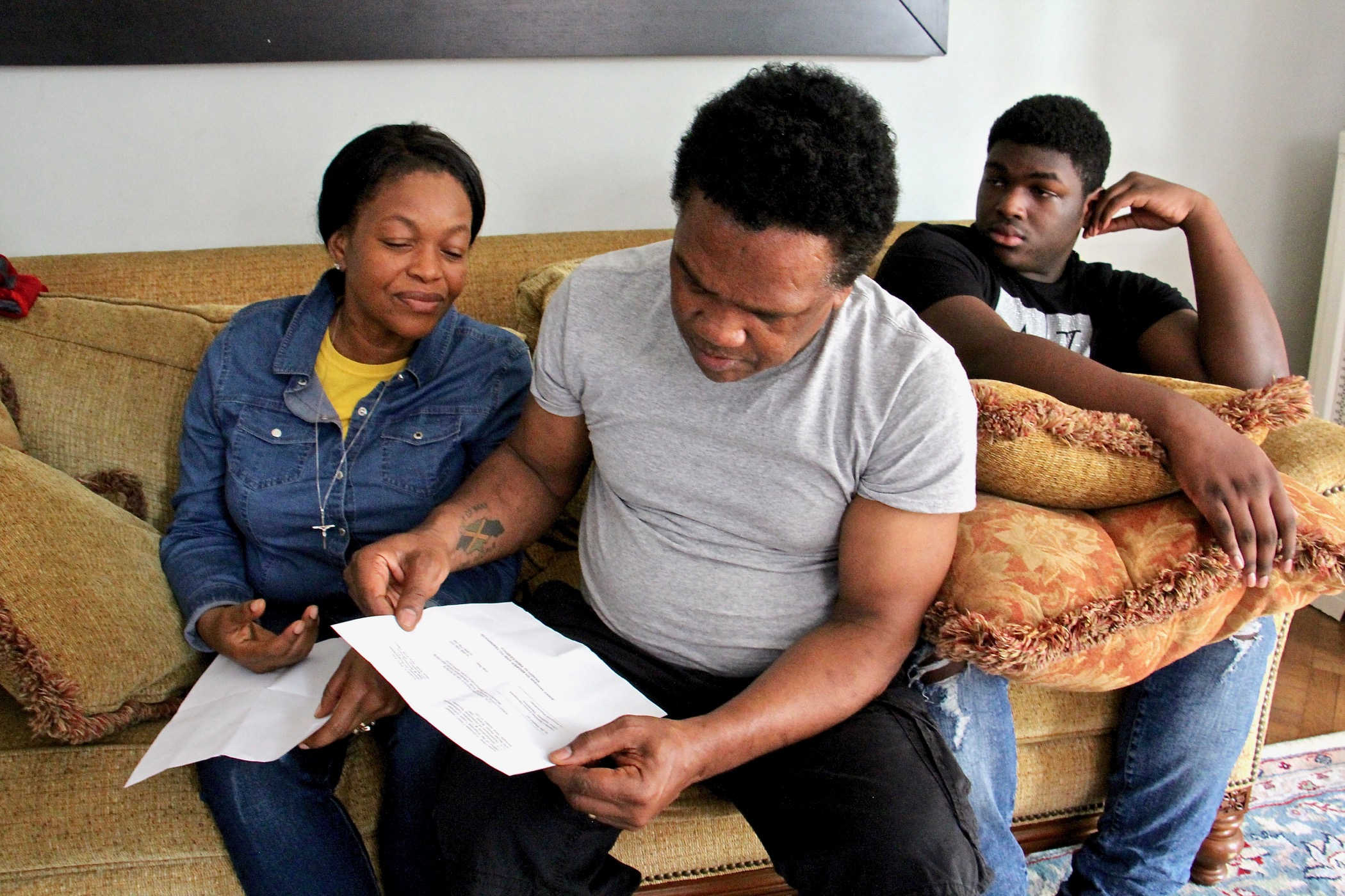 Clive reads a letter while seated next to his wife, Oneita, and son, Timothy, on the couch