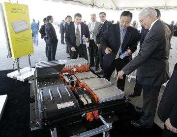FILE- In this file photo made May 26, 2010, people look over the battery array of an all-electric Nissan Leaf in Smyrna, Tenn. Nissan North America, Inc. held its ground-breaking ceremony Wednesday for a lithium-ion battery plant as part of its plan to start building electric cars and eventually create up to 1,300 jobs in Tennessee. The auto industry calls it range anxiety: Drivers want electric cars but worry they won't have enough juice to make long trips. After all, what good is going green if you get stranded with a dead battery? It's a fear that automakers must overcome as they push to sell more battery-powered cars. So government and business are taking steps to reassure drivers by building up the nation's network of electric charging stations. (AP Photo/Mark Humphrey, File)