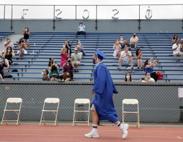 Students walks past applauding friends and family during a graduation ceremony at Millburn High School in Millburn, N.J., Wednesday, July 8, 2020. (AP Photo/Seth Wenig)