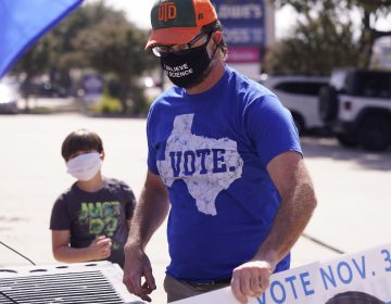 A supporter of Democratic presidential candidate former Vice President Joe Biden prepares for a Ridin' With Biden event Sunday, Oct. 11, 2020, in Plano, Texas. (AP Photo/LM Otero)