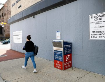 In this July 1, 2020, file photo, a woman walks past a vote-by-mail drop box for the upcoming New Jersey primary election outside the Camden, N.J., Administration Building. (AP Photo/Matt Slocum)