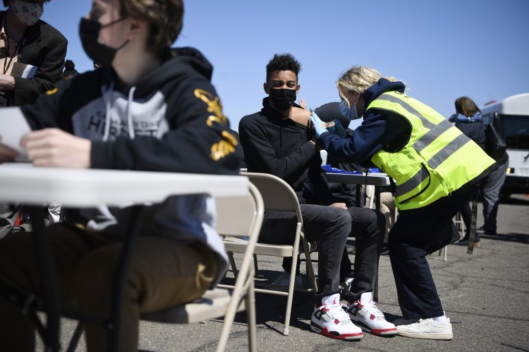 East Hartford High School junior Zander Robinson receives a vaccination from EMT Mary Kate Staunton of Clinton at a mass vaccination site at Pratt & Whitney Runway in East Hartford, Conn., Monday, April 26, 2021. Community Health Center, Inc. (CHC) hosted a
