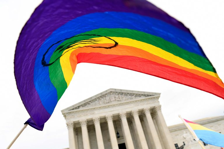 In this Oct. 8, 2019, file photo, protesters gather outside the Supreme Court in Washington. Legislation that would create new protections for LGBTQ Americans is stalling out in the U.S. Senate. Democrats were hopeful they could pass the Equality Act this year since they control Congress and the White House. (AP Photo/Susan Walsh)