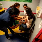 Middle school student Elise Robinson receives her first coronavirus vaccination on Wednesday, May 12, 2021, in Decatur, Ga. (AP Photo/Ron Harris)