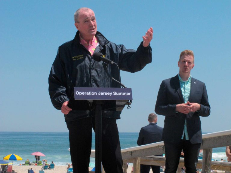 New Jersey Gov. Phil Murphy, left, speaks at a news conference at Island Beach State Park in New Jersey on Wednesday, May 19, 2021, where he announced that the state will give free season-long admission to the park and other state parks to any New Jersey resident who has gotten at least one dose of COVID-19 vaccine by July 4. At right is Shawn LaTourette, the acting environmental protection commissioner. (AP Photo/Wayne Parry)