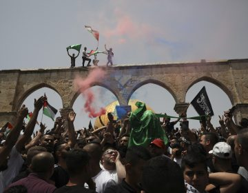 Palestinians wave national flags in front of the Dome of the Rock in the al-Aqsa mosque complex in Jerusalem, Friday, May 21, 202, as a cease-fire took effect between Hamas and Israel after an 11-day war. (AP Photo/Mahmoud Illean)