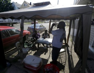 FILE - In this Wednesday, July 4, 2012 file photo, Dave Bailey, right, gulps water from a bottle while hanging inside of a tent on the sidewalk with his sons Daquan Bailey, 14, left, and Davandre Bailey, 17, while beating the heat on Fourth of July in Paterson, N.J. According to a study published Tuesday, May 25, 2021 inNature Communications, during the summer of 2017 in nearly all large urban areas, people of color are exposed to more extreme urban heat than white people. (AP Photo/Julio Cortez, File)