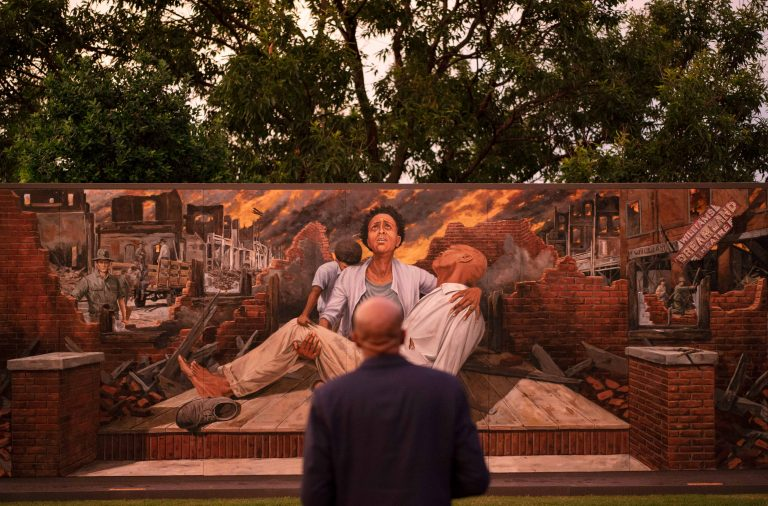 In this Thursday, May 27, 2021 file photo, Darius Kirk looks at a mural depicting the Tulsa Race Massacre in the historic Greenwood neighborhood ahead of centennial commemorations of the massacre in Tulsa, Okla. (AP Photo/John Locher)