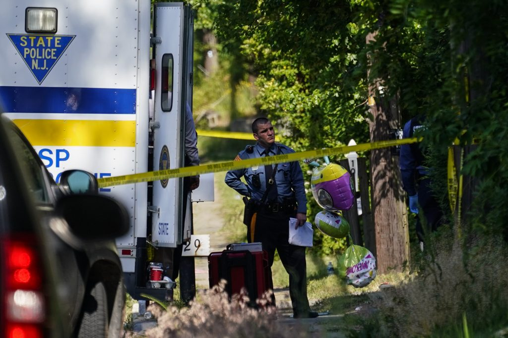 A police officer stands behind crime scene tape