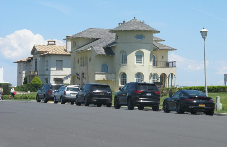 Cars are lined up on an oceanfront street in Deal