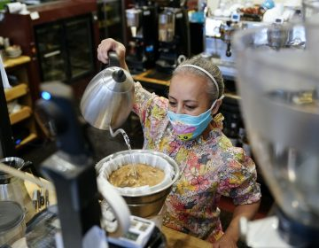 Edna Cruz makes coffee while wearing a mask inside her cafe