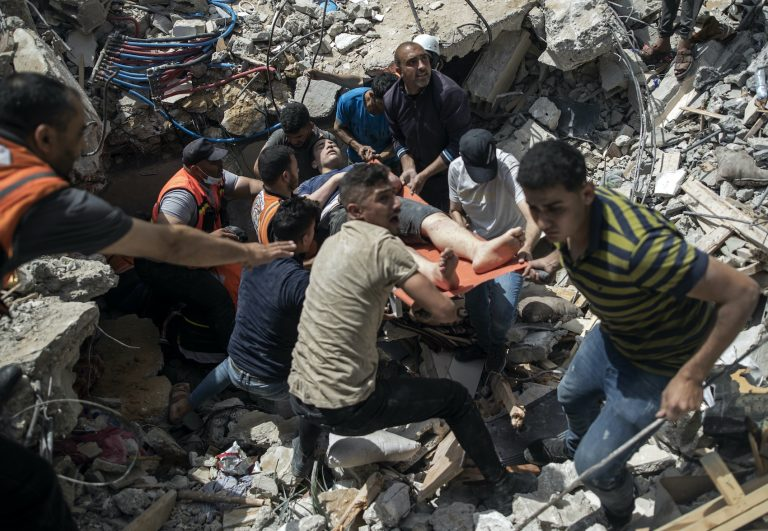 Palestinian rescuers carry a survivor man from under the rubble of a destroyed residential building following Israeli airstrikes
