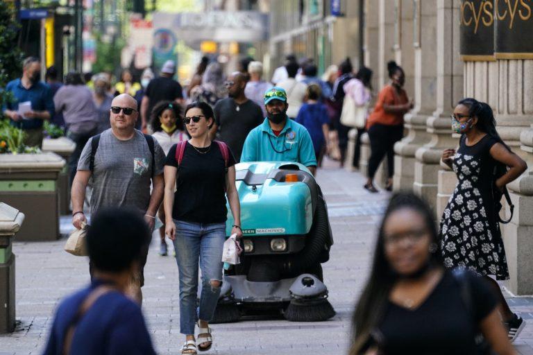 People, some without masks, walk along Market Street