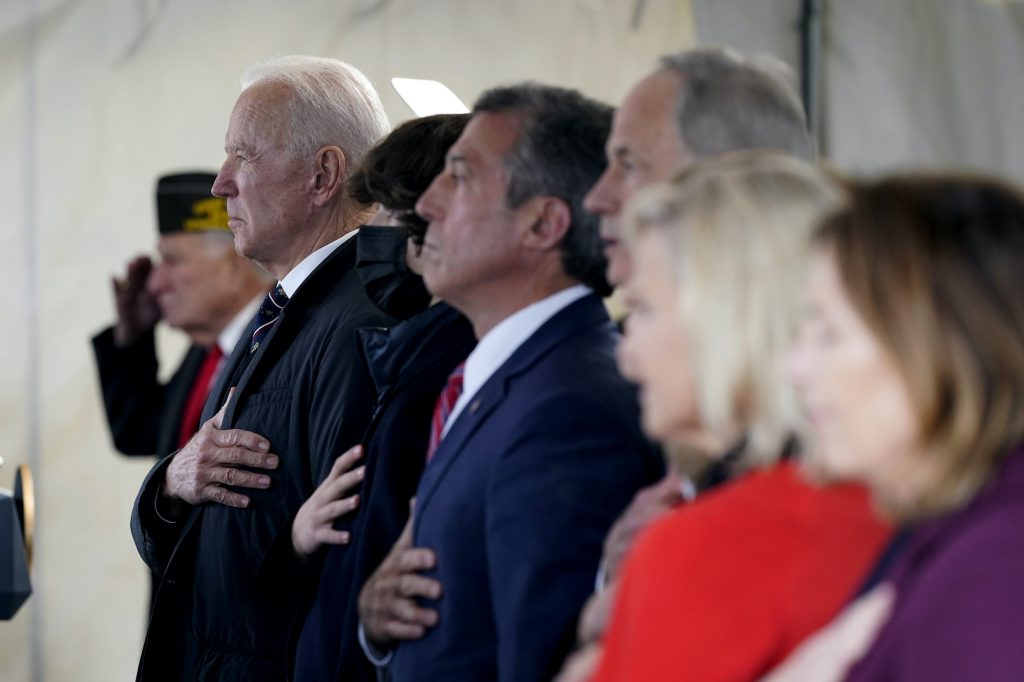 President Joe Biden, Delaware Gov. John Carney, and others stand as a rendition of the national anthem is performed