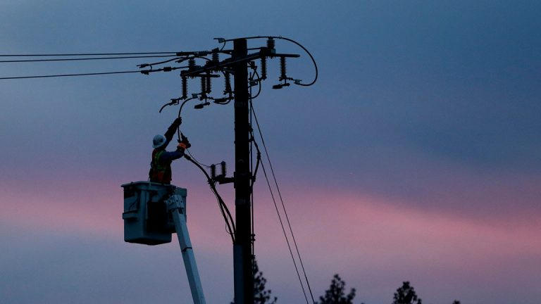 A utility crew member works the lines against a cotton candy sky