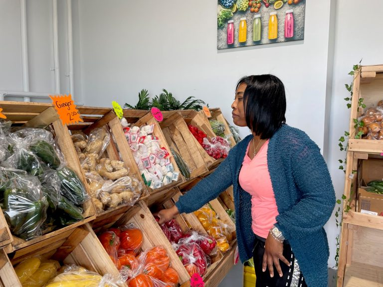Owner Adiyuh Davis inspects the pepper selection. (Cris Barrish/WHYY)