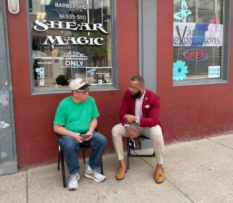 Brandon Flood speaks with a community member outside a barbershop