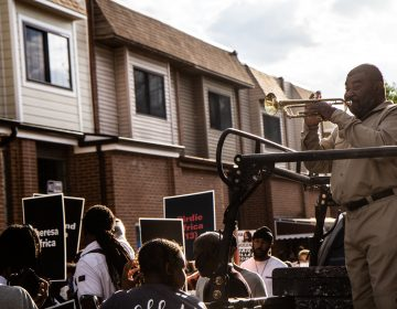 Kenneth Taylor plays the trumpet during a rally to remember the victims of the MOVE bombing