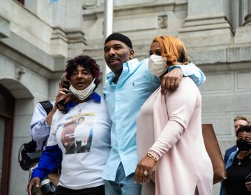 Eric Riddick (center), freed from prison after serving almost 30 years, with his mother Christine Riddick (left) and wife Dana Riddick (right) on May 28, 2021. (Kimberly Paynter/WHYY)
