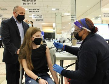Jenna Baron, 12, of Voorhees, N.J., gets her first Pfizer COVID-19 shot from registered nurse Samantha Hickson at the Burlington County mega site in Moorestown. She is accompanied by her father, Robert Baron, a Vice President of operations for Virtua Medical Group. (Emma Lee/WHYY)