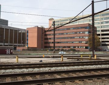 A building is seen beyond railroad tracks