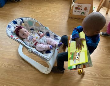 A little boy reads to a baby at a Kinder Academy site in Philadelphia. The baby was the first to return to child care during the pandemic and teachers encouraged the older children to be especially gentle. (Courtesy of Kinder Academy)