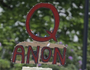 A person carries a sign supporting QAnon during a May 2020 protest rally in Olympia, Wash. (Ted S. Warren/AP)