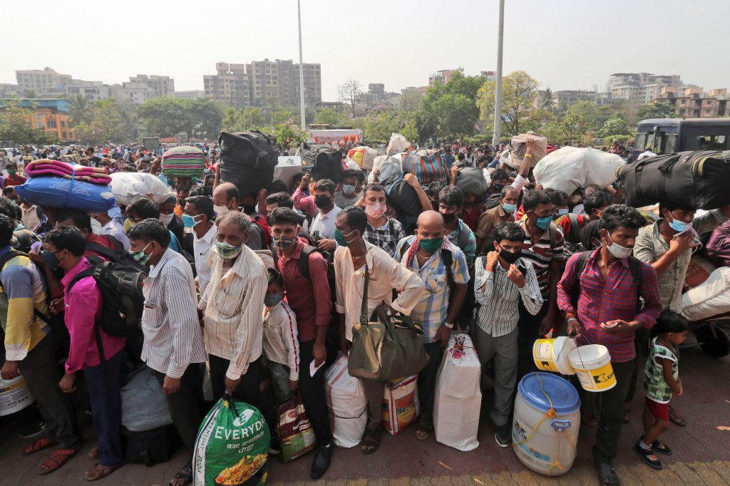People line up to board trains in Mumbai, India, last month. Migrant workers were swarming rail stations in the country's financial capital to go to their home villages as virus-control measures dried up work in the hard-hit region. (Rafiq Maqbool/AP Photo)