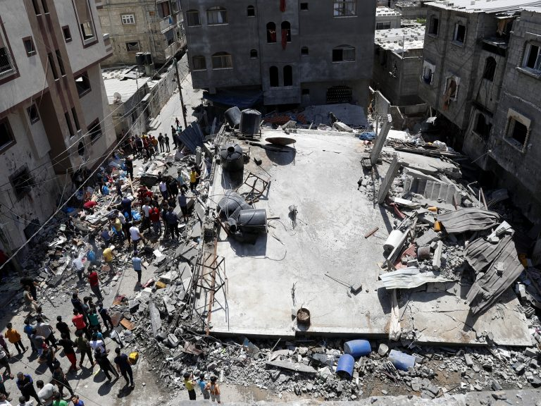 People gather near the rubble of destroyed residential building which was hit by Israeli airstrikes on Thursday in Beit Lahiya, Gaza Strip. (Adel Hana/AP)