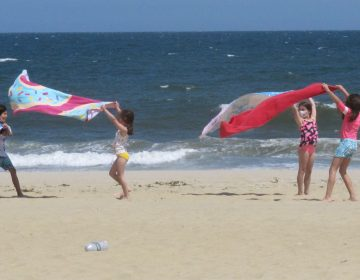 Children play with beach towels on a windy day in Belmar, N.J., on Tuesday. Millions are expected to hit the road or board a plane to celebrate Memorial Day weekend as more people get vaccinated and COVID-19 restrictions are scaled back. (Wayne Parry/AP Photo)
