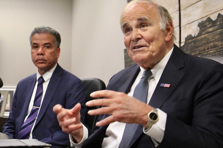 Ed Rendell gestures in the forefround; Carlos Vega sits in the background