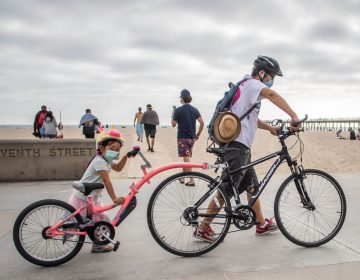 A girl and her father wear face masks while they push their bikes in Hermosa Beach