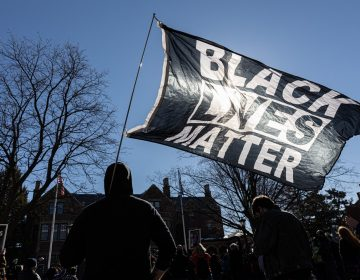 A man holds a Black Lives Matter flag during a protest