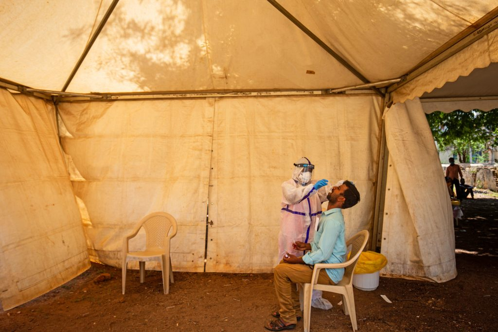A medic performs an oral swab test for the coronavirus this week in Mysore, Karnataka, India. India's prolonged and debilitating wave of infections has reached deep into rural India, where the true extent of devastation may never be known because of a lack of widespread testing or reliable data. (Abhishek Chinnappa/Getty Images)