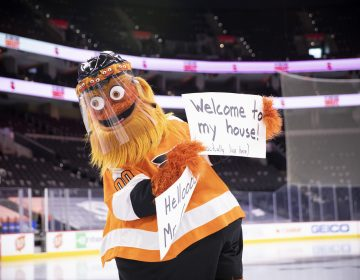 Gritty holds up a sign that says