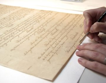 A person's hand holds a pen to the Pa. Constitution