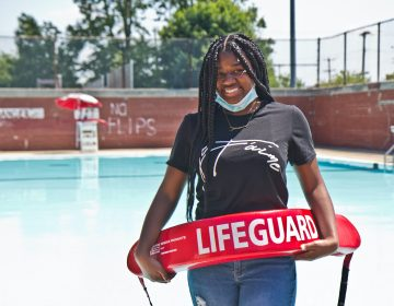 Faith Bradley stands with lifeguard equipment in front of a pool