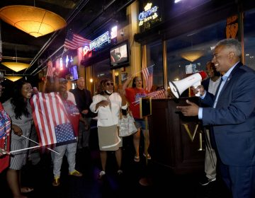 On June 8, interim Camden mayor and candidate Vic Carstarphen claims victory in the Democratic primary at Victor Pub in the city amid cheering supporters. (Photo by April Saul for WHYY)