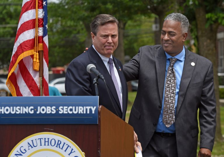 Interim Camden Mayor Vic Carstarphen, at right, who is running in the June 8 primary, shares a podium with US Rep. Donald Norcross, brother of South Jersey political power broker George Norcross, at a June 2 event to announce a $35 million grant to rebuild Ablett Village, a dilapidated Camden housing project. (Photo by April Saul for WHYY)