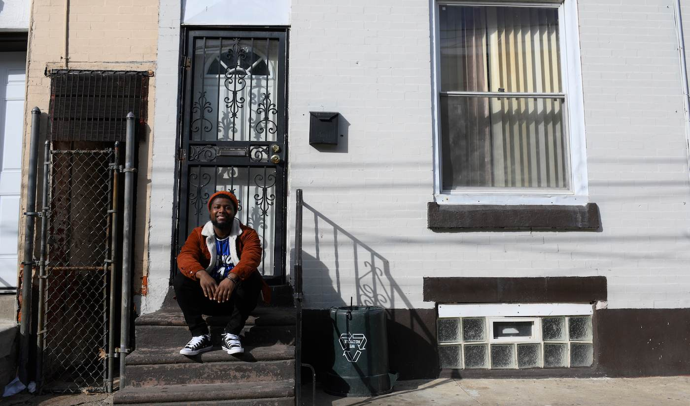 """Shakoor sits in front of his father's childhood home. He sees opportunity on the same Philly streets that nearly destroyed his parents. """"I'm out of the chaos."""" (Bastiaan Slabbers for WHYY)"""