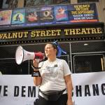 Organizer Jenna Pinchbeck reads the testimonies of those who suffered at the Walnut Street Theater to a crowd of about 80 protesters. (Emma Lee/WHYY)