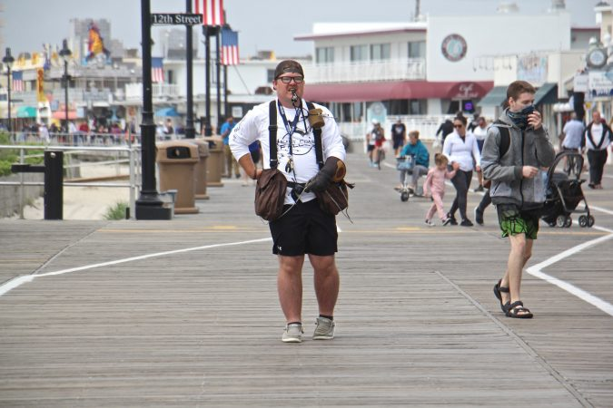 Falconer Ian Turner keeps tabs on his birds as he patrols the Ocean City boardwalk. The presence of birds of prey keeps away seagulls, who often harass outdoor diners. (Emma Lee/WHYY)