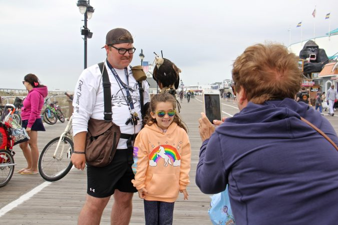 A child poses for a picture with Ian Turner and his Harris's hawk on the Ocean City boardwalk. (Emma Lee/WHYY)