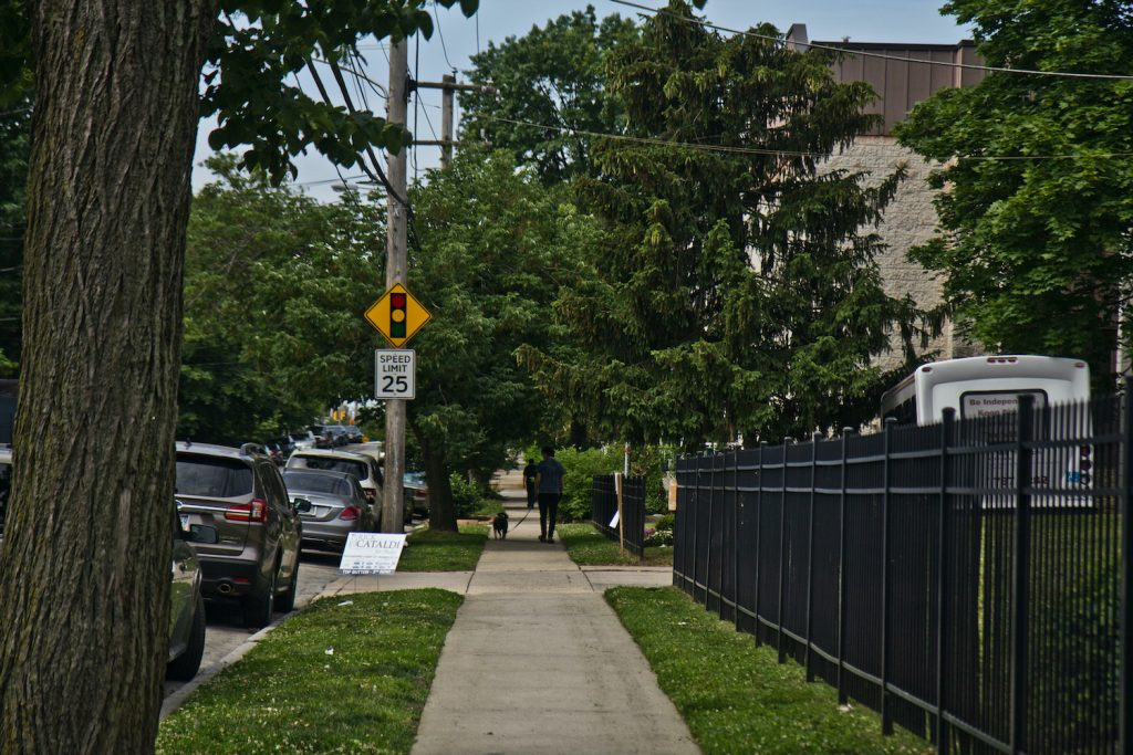 A sidewalk is pictured along a fence on a West Philly street