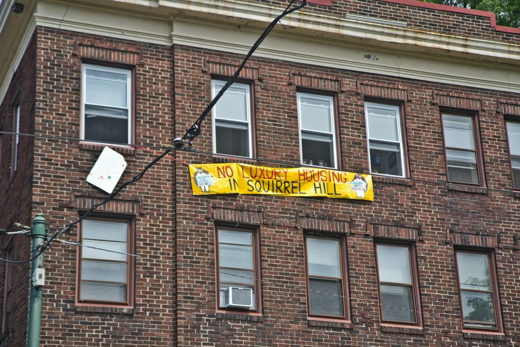 """A sign hung from an apartment window reads, """"No luxury housing in Squirrel Hill"""""""