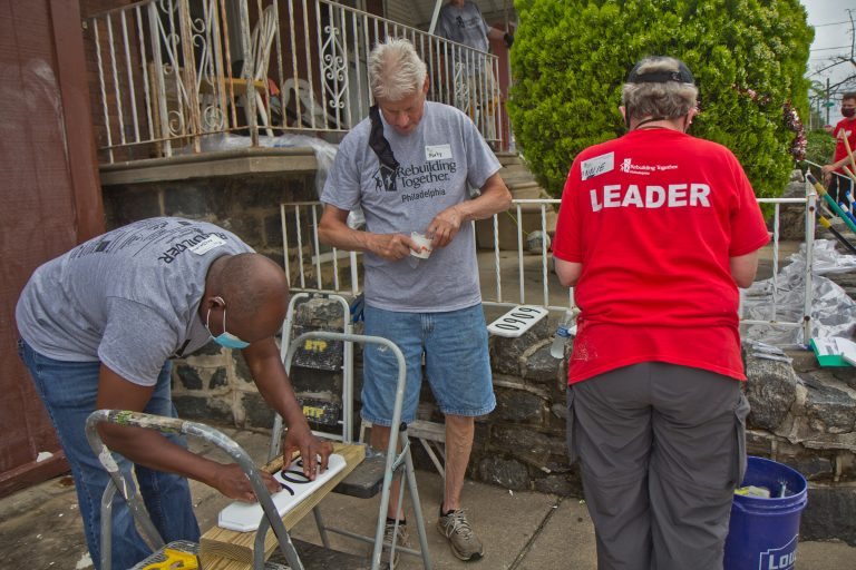 Volunteers with Rebuilding Together Philadelphia create address signs for homes on the 6000 block of Callowhill Street in the city's Haddington neighborhood on June 4, 2021. (Kimberly Paynter/WHYY)