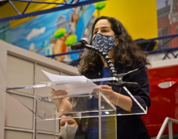 Dr. Cheryl Bettigole speaks from a podium while wearing a face mask