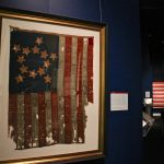 The oldest flag in the exhibit features 13 stars in a star pattern. It is one of the earliest American flags known to survive, made between 1800 and 1825, or possibly earlier. (Emma Lee/WHYY)